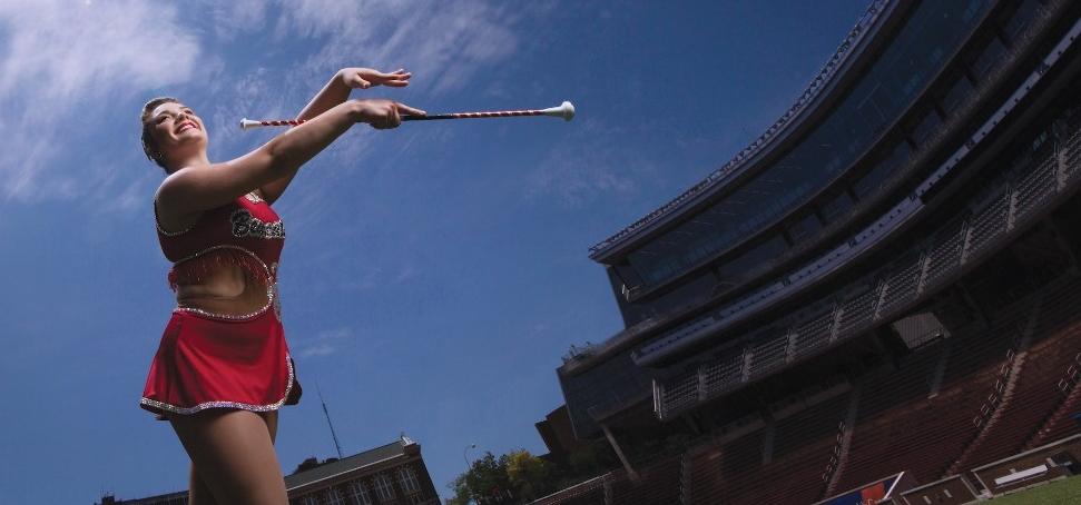 Woman in sequin body suit twirls a baton on a football field