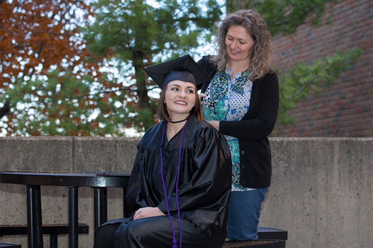 Tori Thomas, in her cap and gown, and her mom Melissa Caldwell on campus