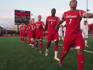 John Manga walks hand in hand onto Gettler Stadium field with the Bearcats team.