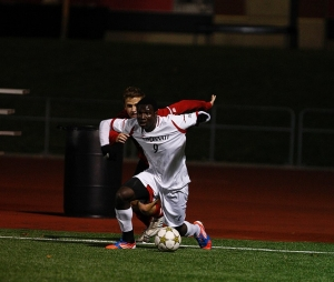 John Manga holds off a soccer defender.