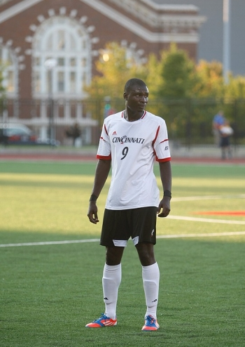 UC soccer player John Manga stands on the field.