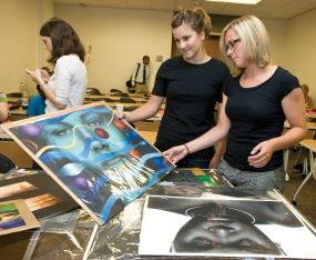 Law students flip through a stack of paintings adimiring the work on Raymond Towler