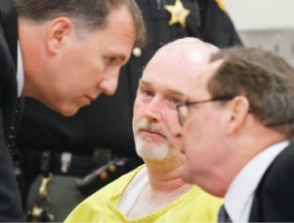 Mark Godsey and Jim Petro lean in to discuss Gillispie's case in front of him, wearing the yellow uniform of a prisoner.
