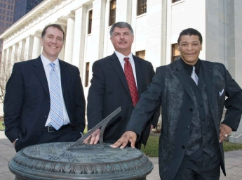 The three men lean against a sundial in front of the statehouse in Columbus.