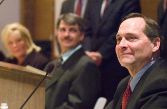 A closeup of Jim Petro's face with Clarence and Melissa Elkins in the background.