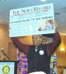 "Gary Reece holds up an oversized News Record newspaper with the banner headline ""Ex-convict thanks UC law students."""