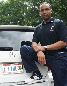 University of Cincinnati alum Lamar Cole, in a Bearcat T-shirt, stands next to his luxury car sporting a Cincinnati Bearcats license plate.