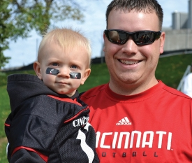 A father and toddler son are dressed in University of Cincinnati garb.