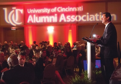 UC President Santa Ono stands at a podium with a dramatic illuminated sign in the background of the UC Alumni Association.