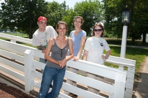 A group of four students pose next to a white four-rail fence at the UC Center for Field Studies.