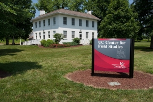 historic Shaker farmhouse sits behind UC Center for Field Studies sign.