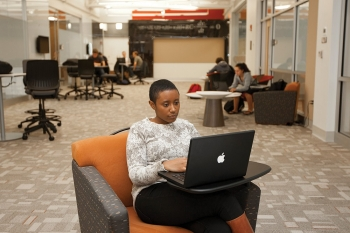 A UC engineering student sits on a cushioned chair looking at her laptop.