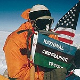 Mountaineer Barry Bishop pins a flag on the top of Mt. Everest.