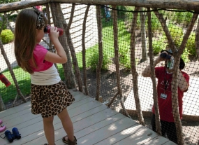 A little girl looks at her father through binoculars.