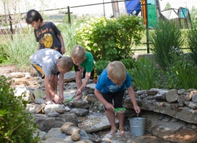 "Four boys wade through the ""brook"" and dig in the rocks."