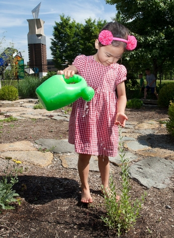 A child pours water from a bucket at UC's PlayScape.