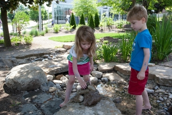 Twins Lily Hope and Abbott Hoffman-Suder stack rocks in a creek bed at UC's PlayScape.