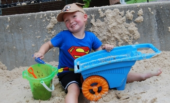 Cody Clark Hamilton plays in the sand at UC's Playscape.