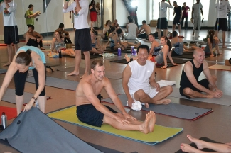 President Ono is seated on a mat as part of a hot yoga class at Yoga Alive.