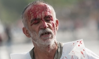 A wounded demonstrater stumbles through Taksim Square after the June 11 police raid.