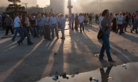 Evening light filters through a cloud of smoke hanging over Taksim Square.