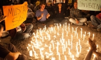 A crowd surrounds a circle of light made only by candles on the ground.