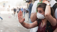 A masked woman puts up her hand as if to say enough