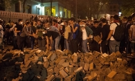 Protesters stand behind a wall of bricks.