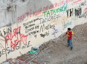 A young bpu reads graffitti on a large imposing wall in Turkey.
