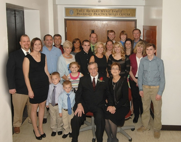 Dick Wuest surrounded by his family members standing in front of the doors of the J. Richard Wuest Family Pharmacy Practice Skills Center at UC.