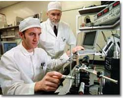 Andrew Steckl and a graduate student work in UC's clean room. photo/Dottie Stover