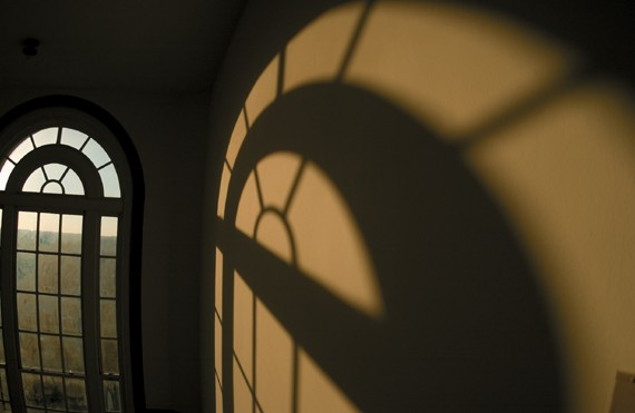 A warm shadow casts across McMicken Hall's main stairwell.