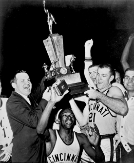 Bearcats coach Ed Jucker and Bob Wiesenhahn (No. 21) hoist the 1961 national championship trophy