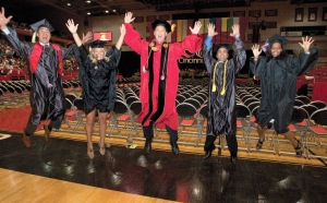 UC President Santa Ono and four recent graduates jump for joy  on the gymnasium court.