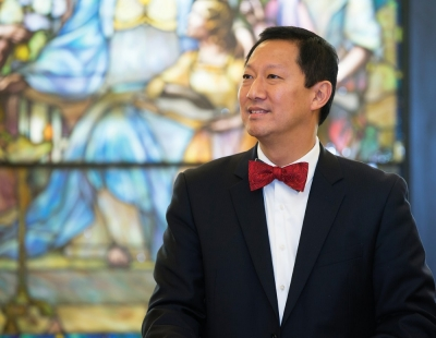 UC President Santa Ono looks reflective next to a stained glass window.