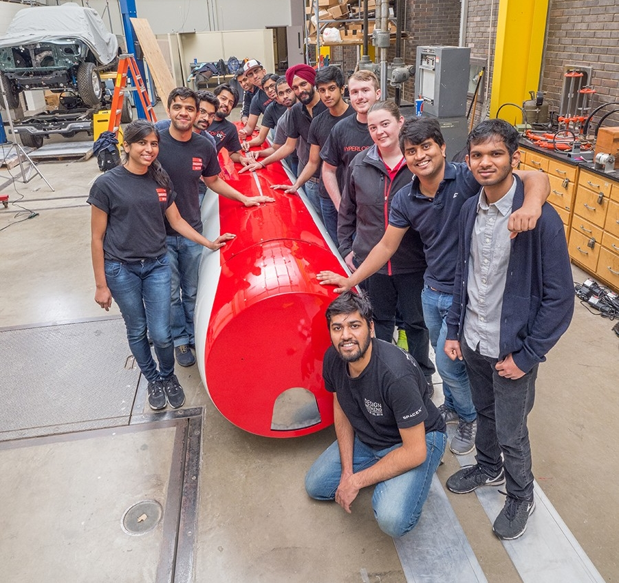 Hyperloop UC team gathers with pod in the Rhodes Hall High Bay at UC.