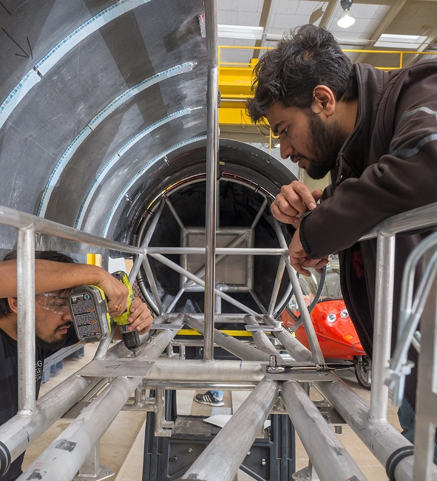 Hyperloop UC team members make final changes to their prototype after its return from painting.