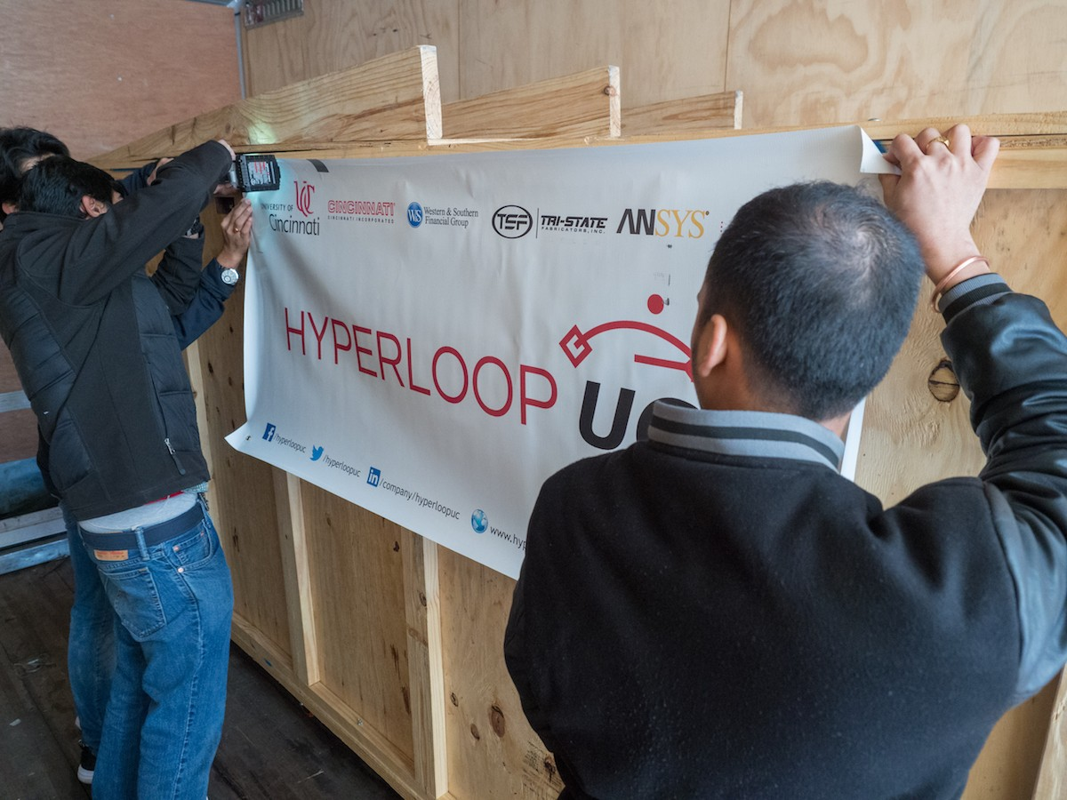 UC students attache the UC Hyperloop banner to the side of the shipping crate.