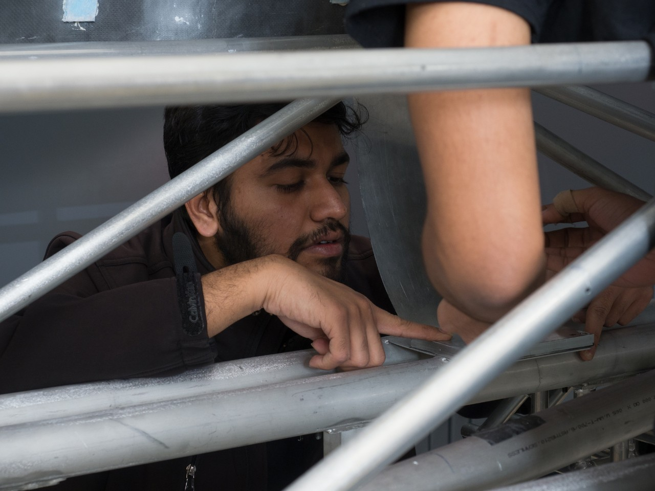 Hyperloop UC team leader Dhaval Shiyani inspects the details of their space frame in the final week before shipping it to California.